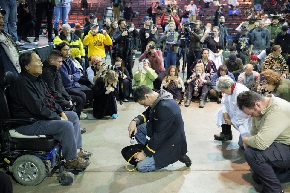 Gen. Wesley Clark Jr., middle, and other veterans kneel in front of Leonard Crow Dog during a forgiveness ceremony at the Four Prairie Knights Casino & Resort on the Standing Rock Sioux Reservation on Monday, Dec. 5, 2016. Photo by Josh Morgan, Huffington Post